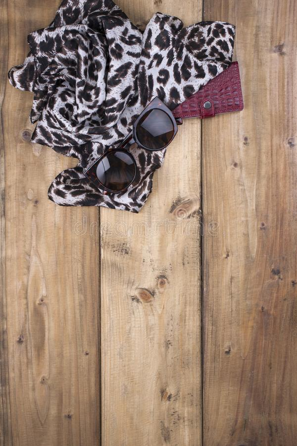 Scarf with leopard print, sunglasses and a purse made of red leather on a wooden background. Natural colors and natural ornament. In fashion. Free space for stock image