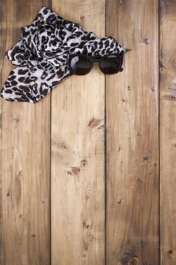 Scarf with leopard print and sunglasses on a wooden background. Natural colors and natural ornament in fashion. Free space for. Text. Top view royalty free stock photo