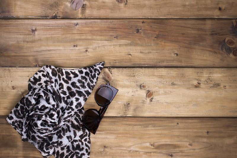 Scarf with leopard print and sunglasses on a wooden background. Natural colors and natural ornament in fashion. Free space for. Text. Top view stock photos