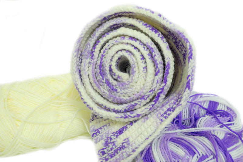 Scarf Multicolored ball of yarn. Handmade knitted scarf made from purple knitting yarn royalty free stock photos