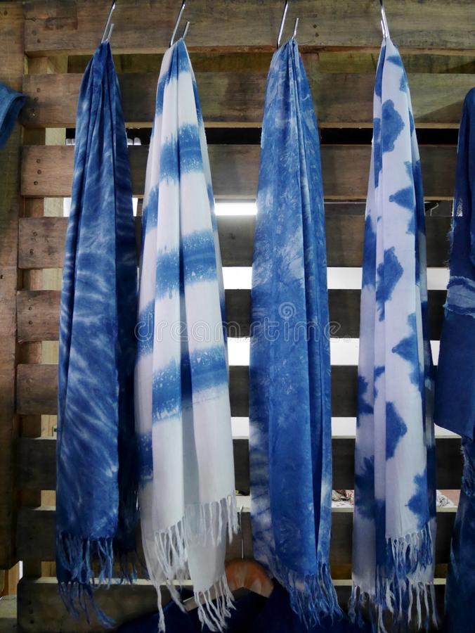 Scarf and shawl tie batik dyeing with mauhom indigo hanging on wooden wall in clothes shop at market in Nonthaburi, Thailand royalty free stock photo