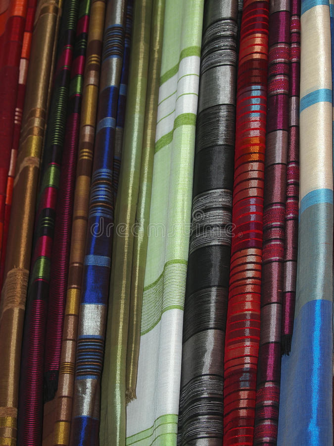 Scarfs on open market. Pile of gentle folded shawls (scarfs) at the market stock photo