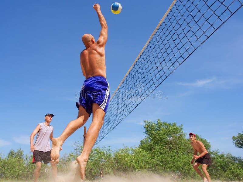 Scarica della spiaggia del gioco dei tre uomini fotografia stock