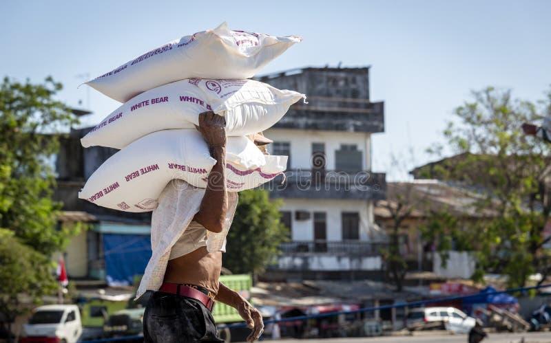 Scaricando un camion e trasporto delle quelle borse pesanti ad una nave fotografia stock libera da diritti