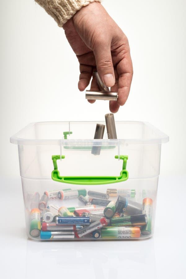 Scarichi le batterie da riciclare, mano che getta il batteri di aa fotografie stock libere da diritti