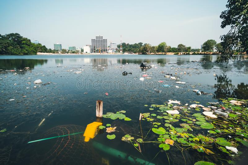 Scarico della città nello stagno in parco L'immondizia si trova nell'acqua su una del paesaggio urbano le bottiglie di plastica s fotografia stock libera da diritti
