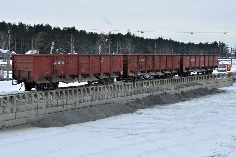 Scarico della pietra schiacciata un'automobile ferroviaria di un autocarro con cassone ribaltabile, primo piano Scarico del caric fotografia stock