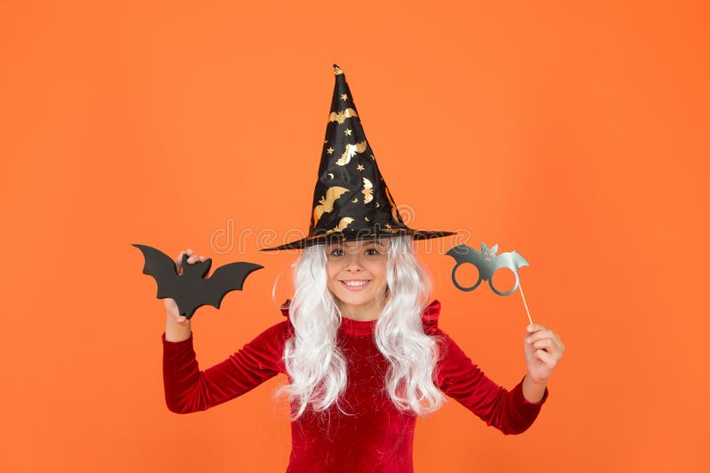 The scariest party tonight. Party girl with Halloween props orange background. Small child wear wicked witch party. Costume. Halloween kid with party look stock photos