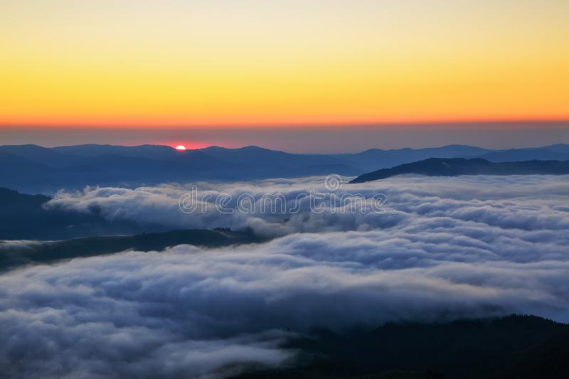 Scarlet sun at a dawn, which seems to swim out from the mountain peaks, coloring boundless sky in orange shades. Scarlet sun at a dawn, which seems to swim out royalty free stock photography