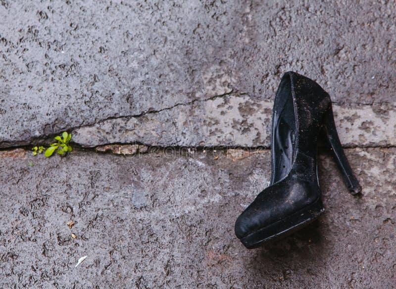 Scarpa abbandonata della pompa con su asfalto immagine stock libera da diritti