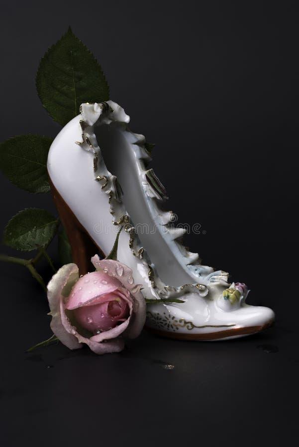 Scarpa d'annata del tacco alto della porcellana con la rosa rosa bagnata fotografia stock