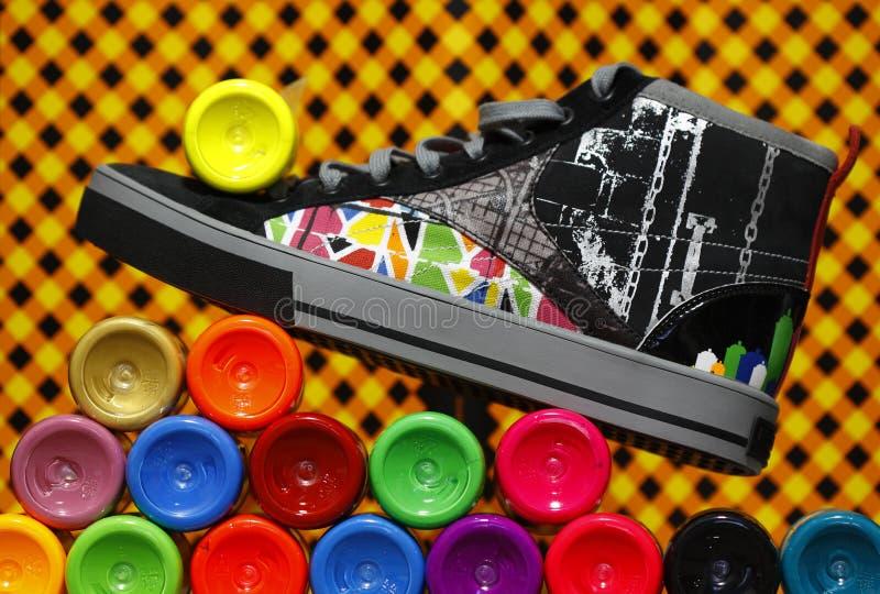 Scarpa da tennis di colore che si leva in piedi sulle bottiglie della vernice fotografia stock libera da diritti