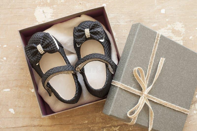 Scarpa di bambino in contenitore di regalo su fondo di legno immagine stock libera da diritti