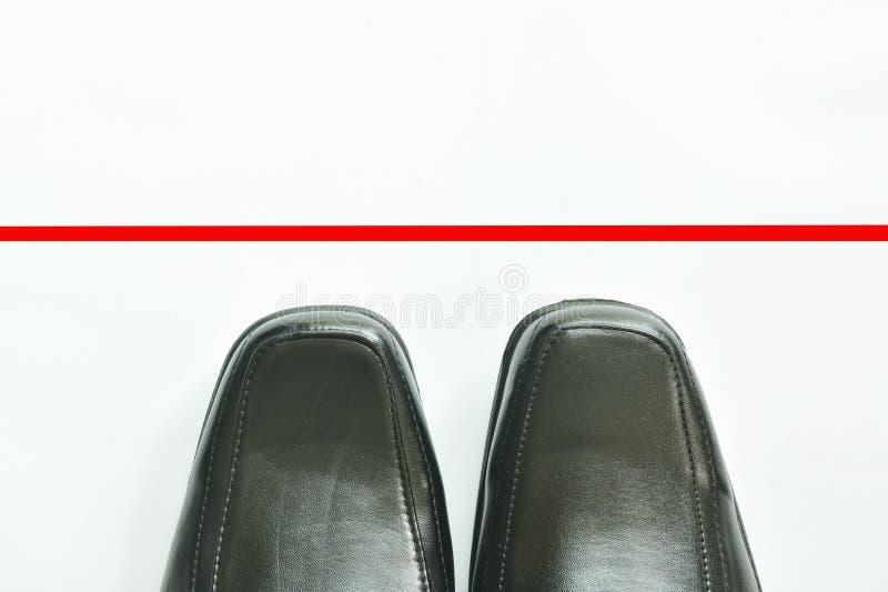 Scarpa di cuoio di affari neri con la linea rossa da oltrepassare su fondo bianco immagini stock