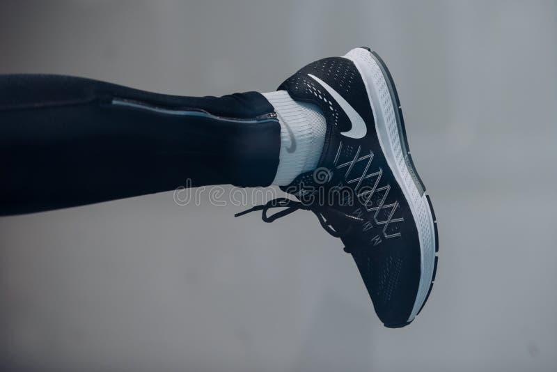 Scarpa di sport sulla gamba Scarpa da corsa con il calzino sulla sogliola Istruttore o scarpa da tennis Calzature e modo di sport immagini stock libere da diritti