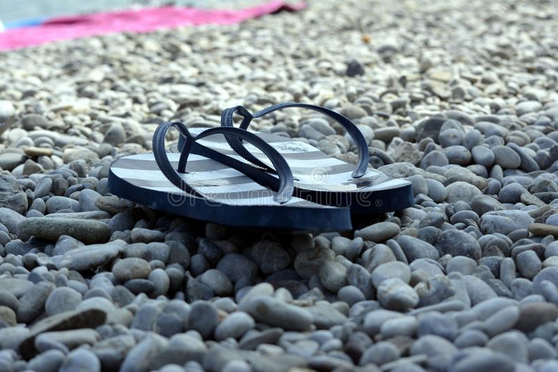 Scarpe all'aperto per la spiaggia sulle rocce fotografia stock libera da diritti