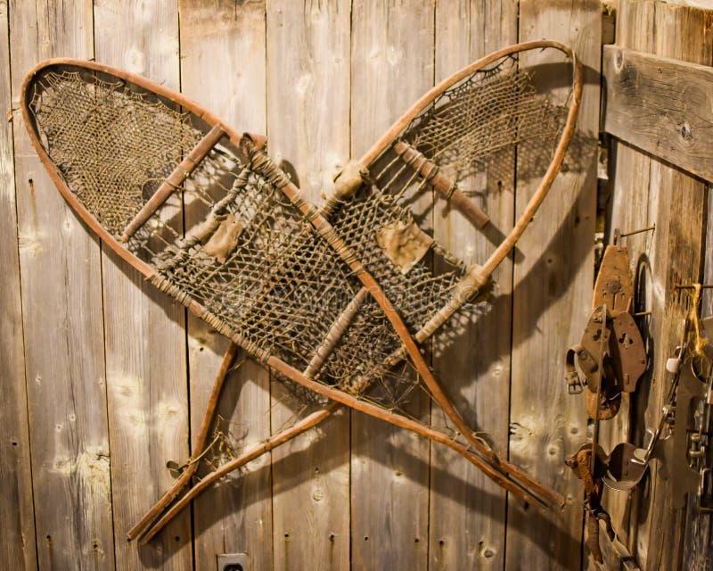 Scarpe antiche della neve che appendono sulla parete di legno immagini stock