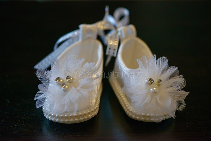 Scarpe bianche adorabili della neonata con i dettagli della perla e le decorazioni frizzanti immagini stock libere da diritti