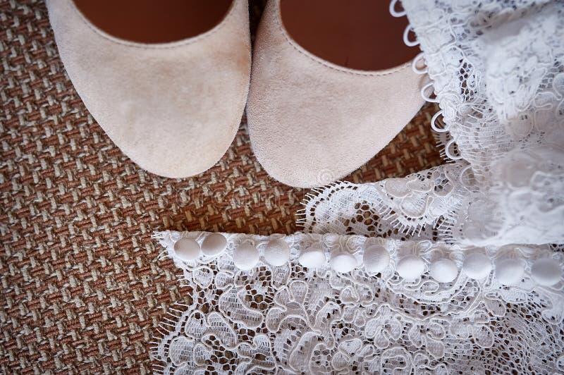 Scarpe bianche della sposa e del vestito fotografia stock