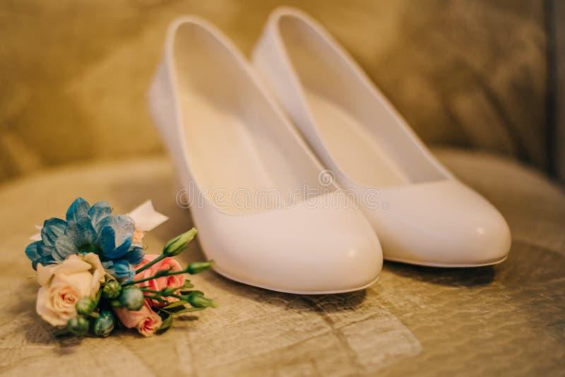 Scarpe bianche di festa per la sposa con un occhiello con i fiori reali immagine stock