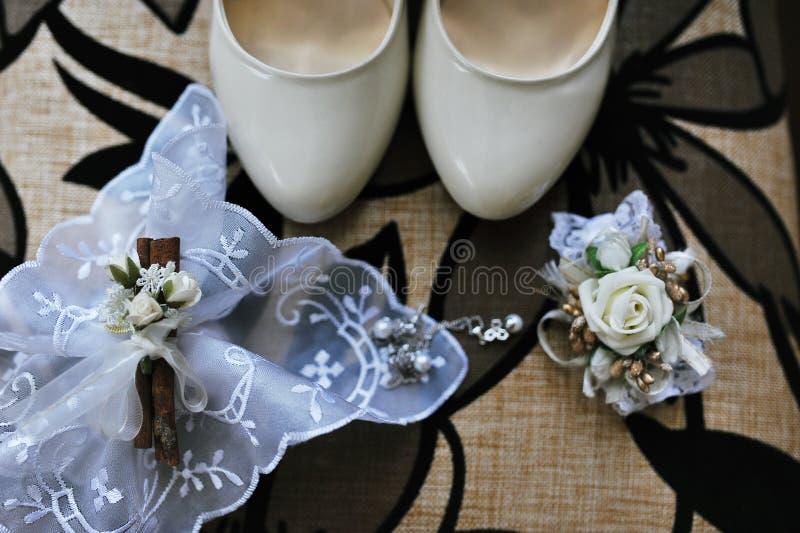 Scarpe bianche di nozze per la sposa con gli accessori fotografia stock libera da diritti