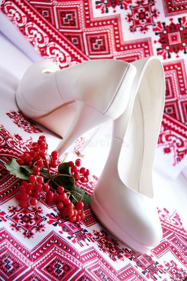 Scarpe bianche di nozze su un fondo dell'ucranino del ricamo fotografia stock libera da diritti