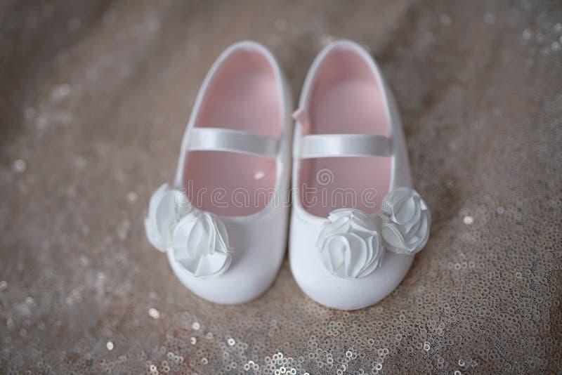 Scarpe bianche eleganti della ballerina per le bambine o bottini della neonata con i fiori chiffoni bianchi e la cinghia con elas immagini stock libere da diritti