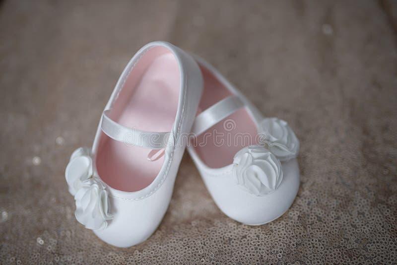 Scarpe bianche eleganti della ballerina per le bambine o bottini della neonata con i fiori chiffoni bianchi e la cinghia con elas fotografie stock