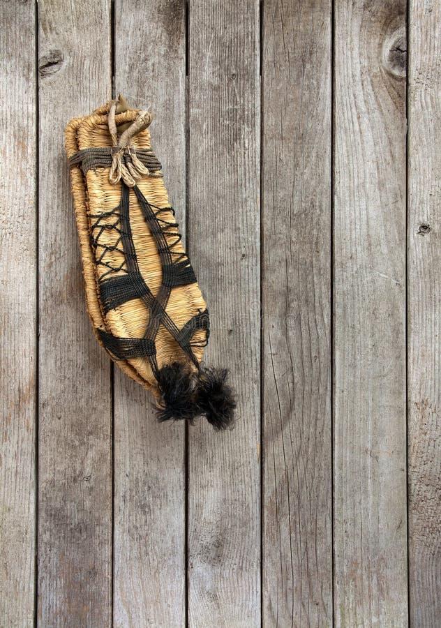 Scarpe d'annata della paglia del cinese tradizionale sul bordo di legno fotografie stock