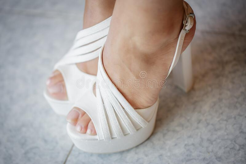Scarpe da sposa Bellissime gambe - Concetto di matrimonio fotografia stock libera da diritti