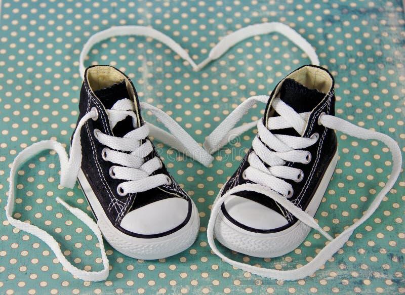 Scarpe da tennis con il cuore del laccetto immagini stock
