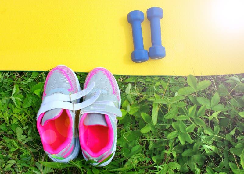 Scarpe da tennis delle scarpe di sport su erba verde su un prato della molla fotografia stock