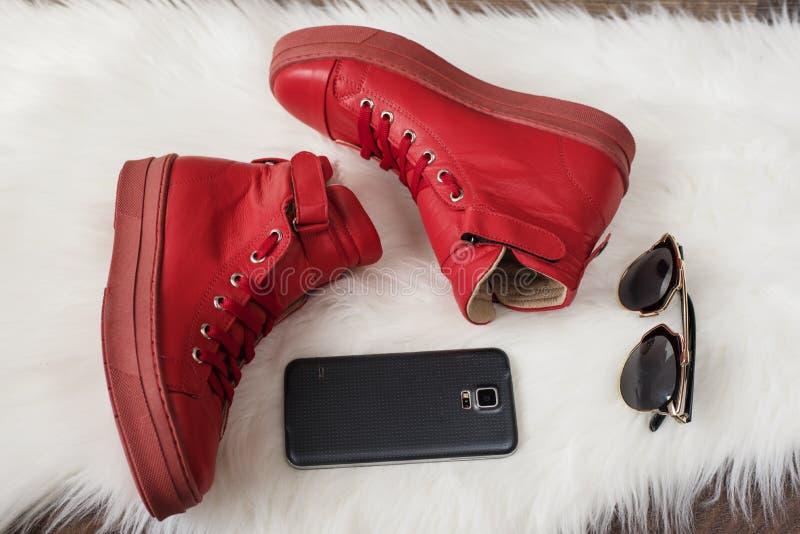 Scarpe da tennis di cuoio rosse, telefono cellulare, occhiali da sole su un tappeto bianco fotografia stock libera da diritti