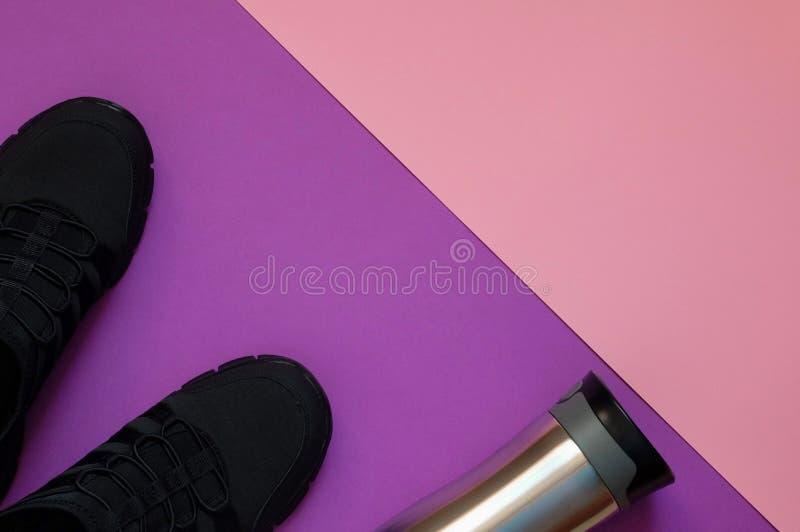 Scarpe da tennis e bottiglia nere del metallo sullo spazio geometrico viola e di corallo della copia del whith del fondo fotografie stock