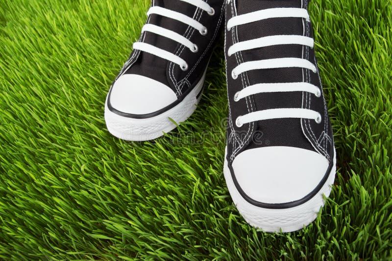 Scarpe da tennis nel campo di erba immagini stock