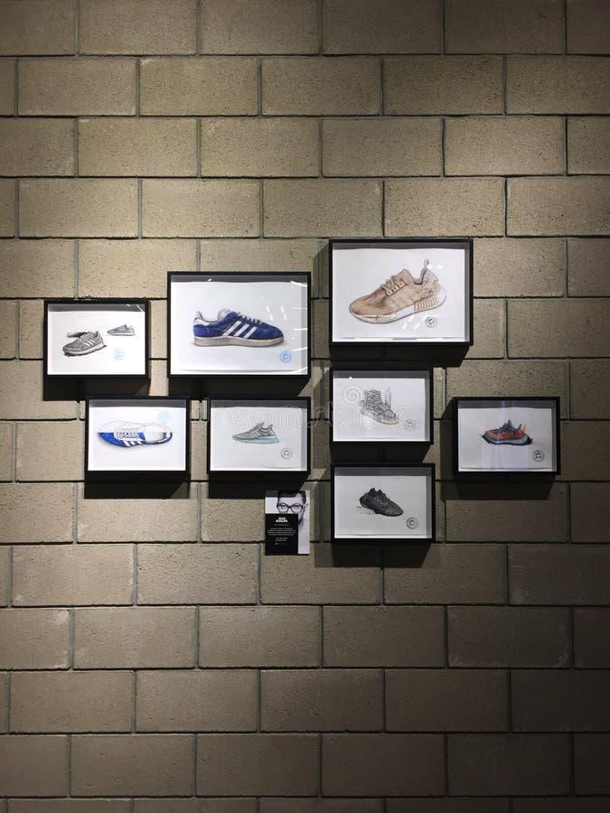 Scarpe da tennis pagina di Adidas su un muro di mattoni fotografia stock libera da diritti