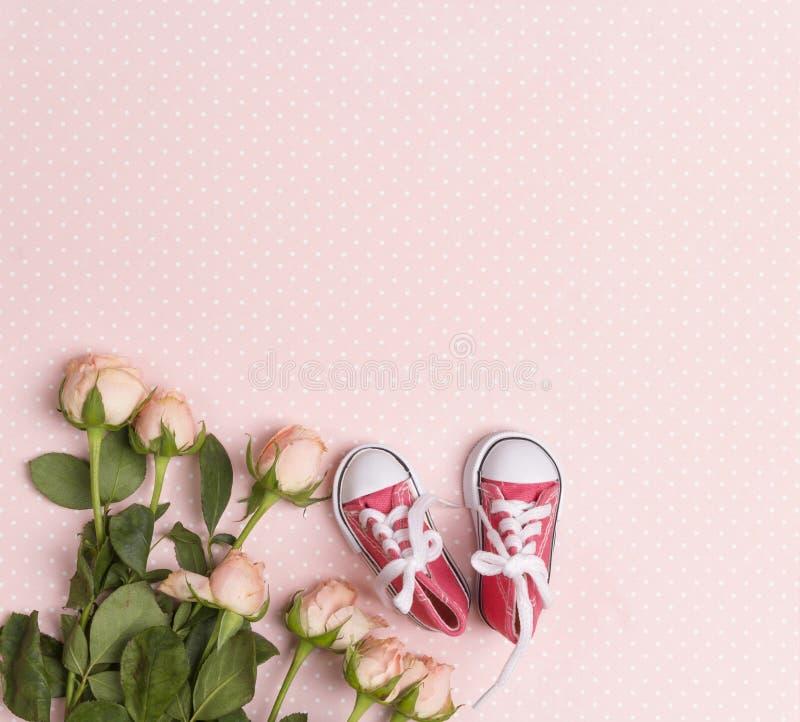 Scarpe da tennis rosa della neonata con i piccoli fiori rosa su un fondo rosa fotografie stock libere da diritti