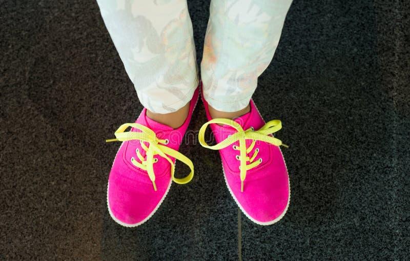 Scarpe da tennis rosa sulla ragazza, gambe della giovane donna immagini stock libere da diritti