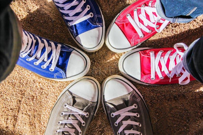Scarpe da tennis rosse, blu e grige che stanno nel cerchio sulla sabbia asciutta, vista da sopra Raggiro di amicizia, di modo, di immagine stock libera da diritti