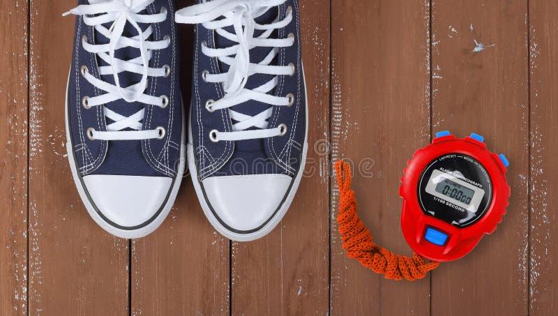 Scarpe dei vestiti e sport - gumshoes blu di paia del frammento di vista superiore e fondo di legno del cronometro rosso fotografie stock