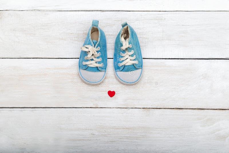 Scarpe del blu di bambino su fondo di legno Disposizione piana fotografia stock