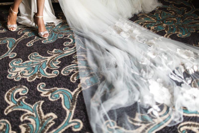 Scarpe del primo piano, gambe, vestito e velo nuziali, migliori accessori per la sposa per la preparazione di mattina di nozze fotografie stock libere da diritti