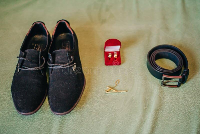 Scarpe del ` s degli uomini, cinghia di cuoio per i pantaloni, fedi nuziali in una scatola rossa e supporto di un legame, attribu immagine stock