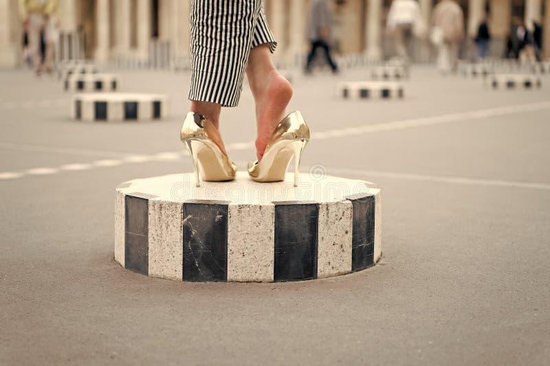 Scarpe del tacco alto sui piedi femminili sul quadrato di città Gambe in scarpe dorate Parigi, Francia di fascino Scarpe di modo  fotografia stock