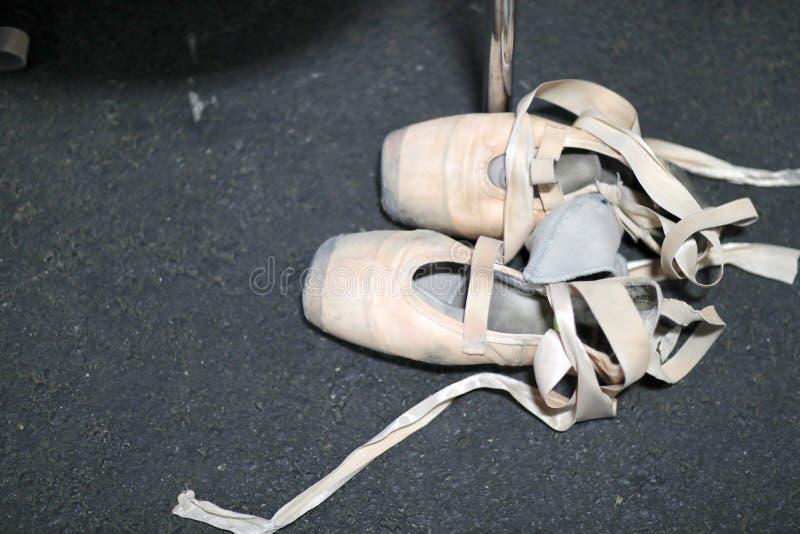 Scarpe di balletto della ripetizione della ballerina con i nastri e gli elastici fotografie stock