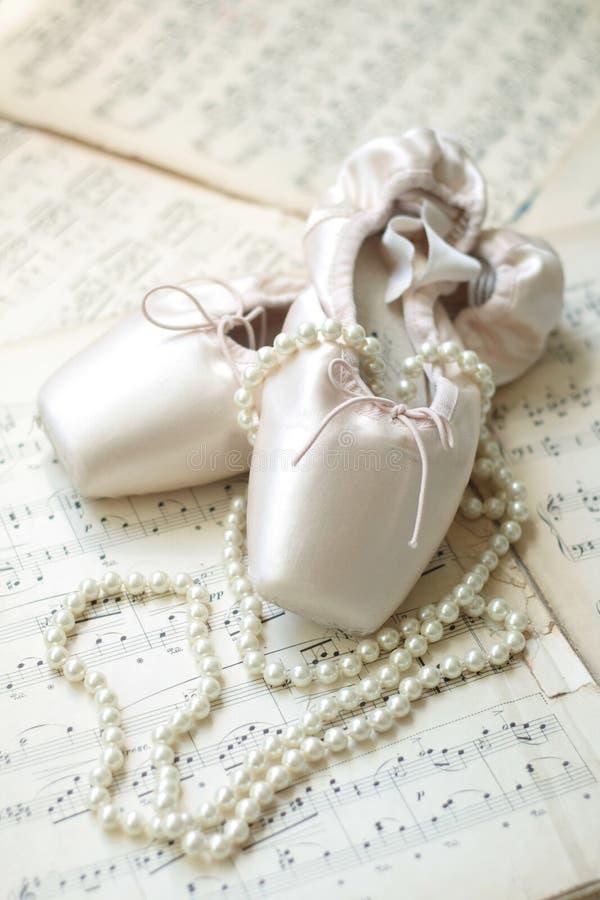 Scarpe di balletto e collana della perla sulle note musicali fotografie stock libere da diritti