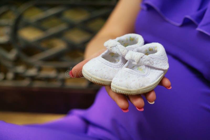 Scarpe di bambino della tenuta della donna incinta sulla sua mano fotografia stock libera da diritti