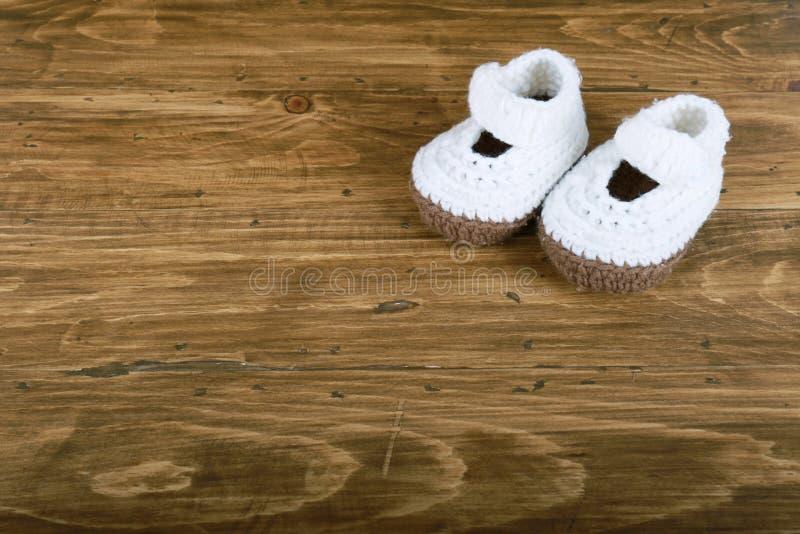 Scarpe di bambino fatte a mano tricottate su fondo di legno immagini stock libere da diritti
