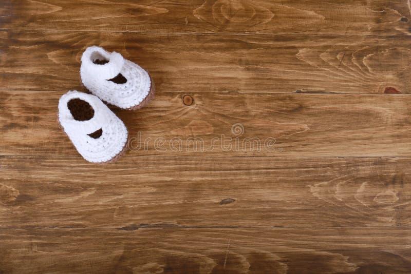 Scarpe di bambino fatte a mano tricottate su fondo di legno fotografie stock