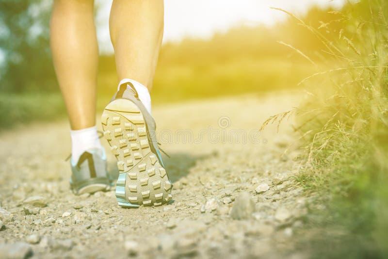 Scarpe di camminata, sport e forma fisica dei insports della donna all'aperto fotografie stock